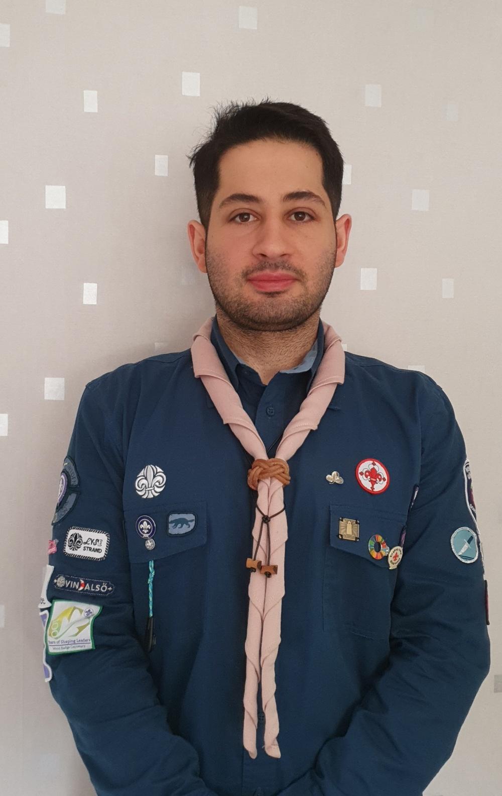Halvkroppsporträtt på George Chamoun i scoutklädsel.