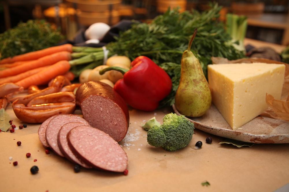 Grönsaker, frukt och korv på ett bord