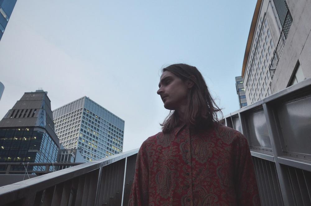 Grodperspektiv på en man som står vid höga skyskrapor