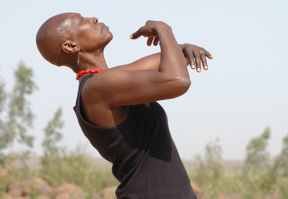 En äldre, svart kvinna står i profil i ett landskap bland låga träd och brun lera. Hon står lätt bakåtlutad med händerna i en dansande rörelse framför bröstet. Hon har en svart ärmlös klänning och ett korallrött halsband bestående av runda stenar.