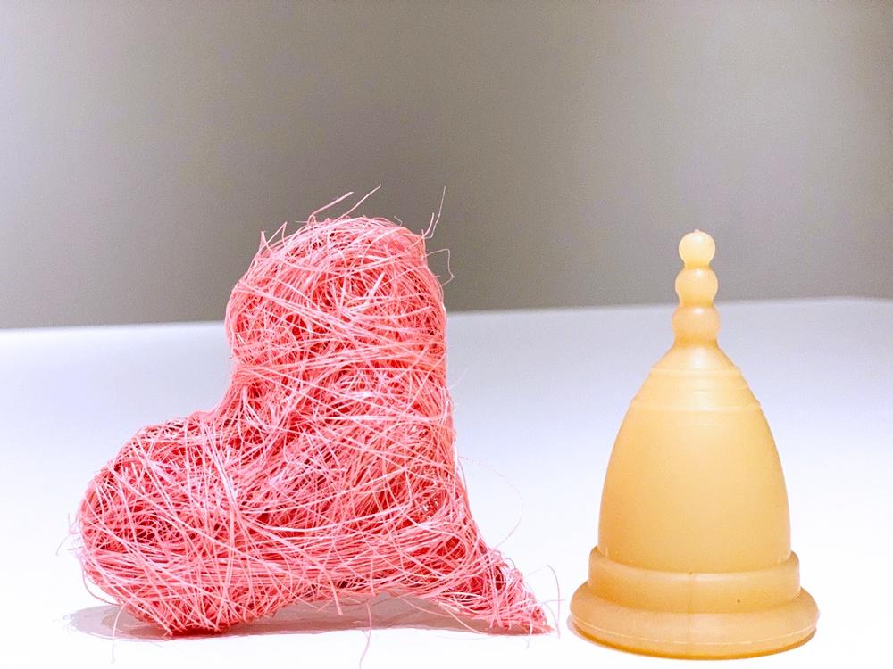 Närbild på en menskopp sm står bredvid ett rosa hjärta.