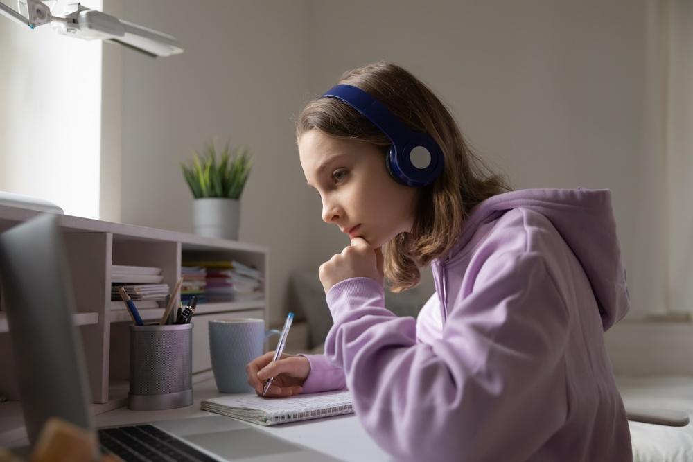 Bild på flicka som sitter vid sitt skrivbord framför datorn och deltar i lektion.