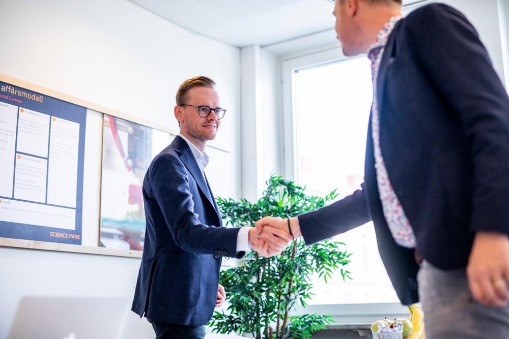 Science Parks VD Gustav Österström skakar hand med man i svart kavaj