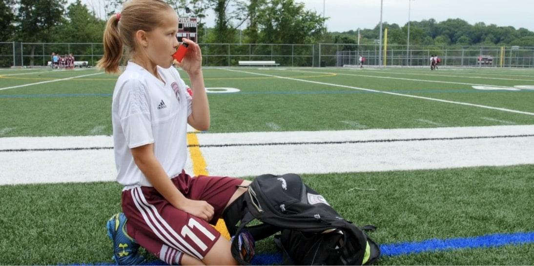 Izzy taking her inhaler on the field