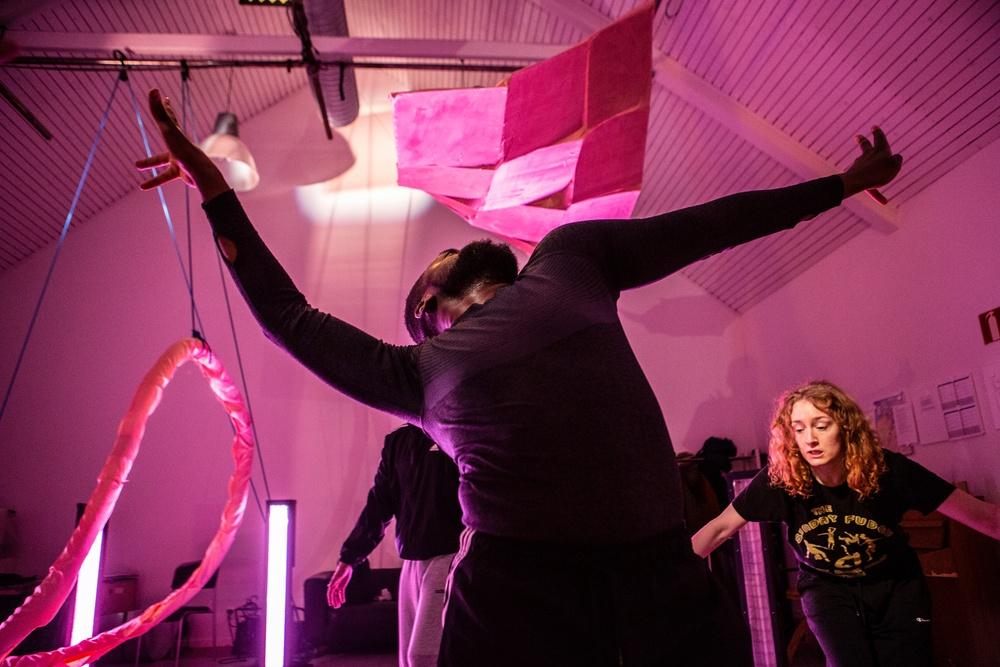 Tre dansare rör sig, med stora rörelser, i ett rosafärgat rum.
