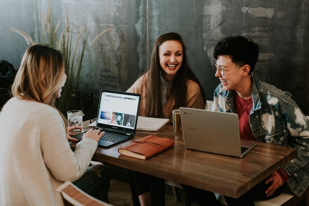 Glada personer som sitter vid ett bord med sina datorer och studerar tillsammans.