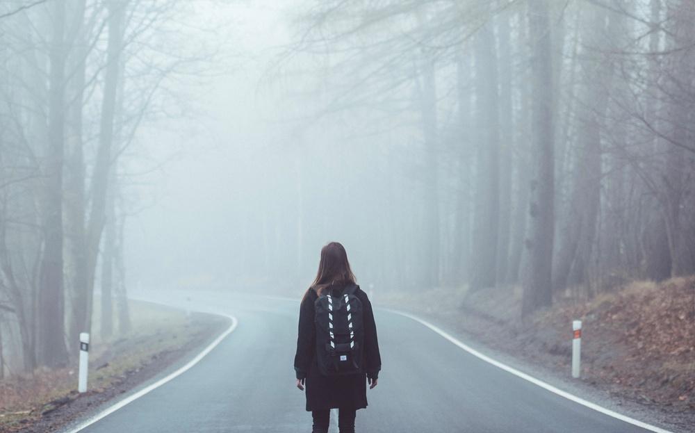 Ensam person i dimma vid en vägkurva