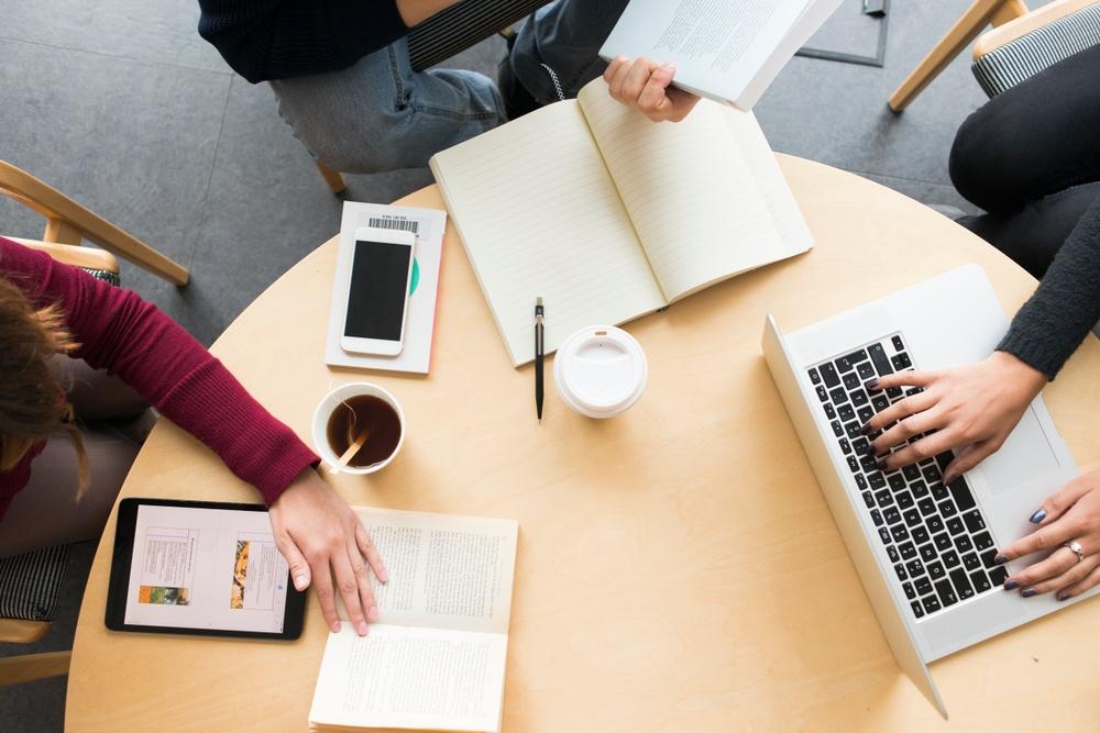 Tre personer arbetar med dator och anteckningsblock