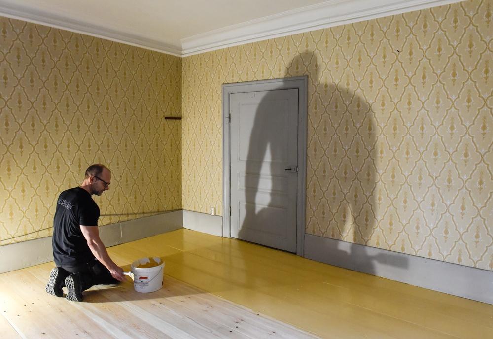 Kulturens målare Rickard Öhman målar matsalsgolvet gult. I arkivmaterial har vi hittat information om att matsalsgolvet var gult när familjen Thomander bodde i huset, och i samband med restaureringen passade vi på att rekonstruera den detaljen. Innan restaureringen var golvet av obehandlat trä. Foto: Viveca Ohlsson/Kulturen