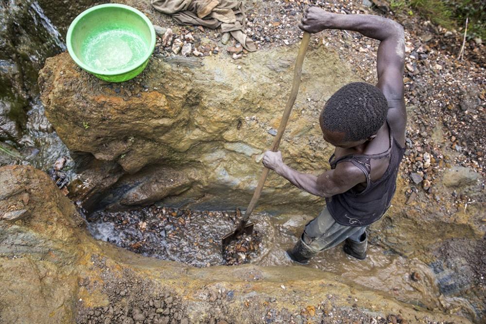 Person står och arbetar hårt i ett lerigt vattendrag med en spade.