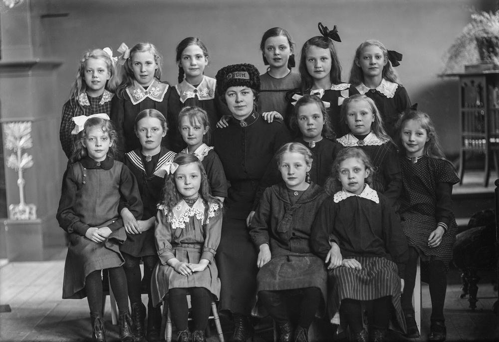 Kvinna i Frälsningsarméns uniform och flickor från barnkåren. Foto:  Ida Ekelund, ur Kulturens samlingar.