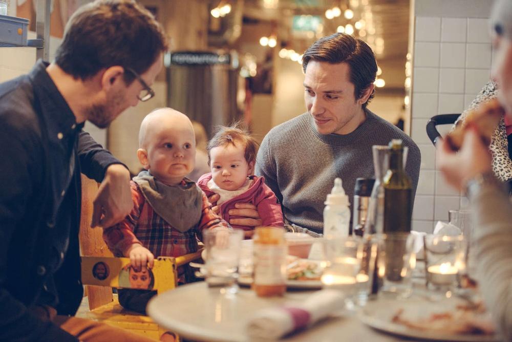 Två män och deras barn besöker restaurang i Stockholm.