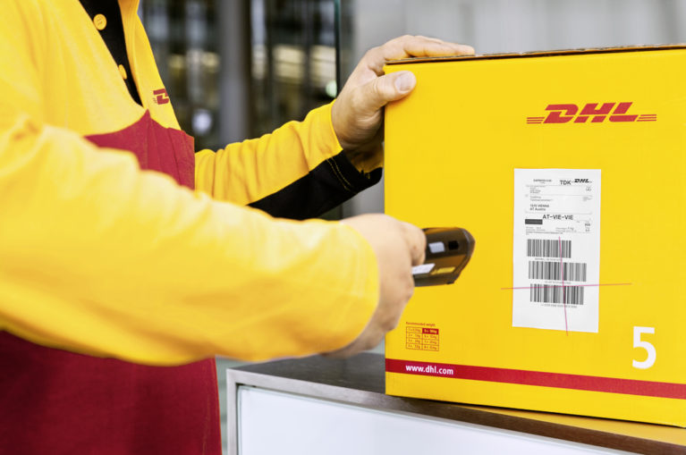 DHL staff scanning tracking code on yellow DHL package