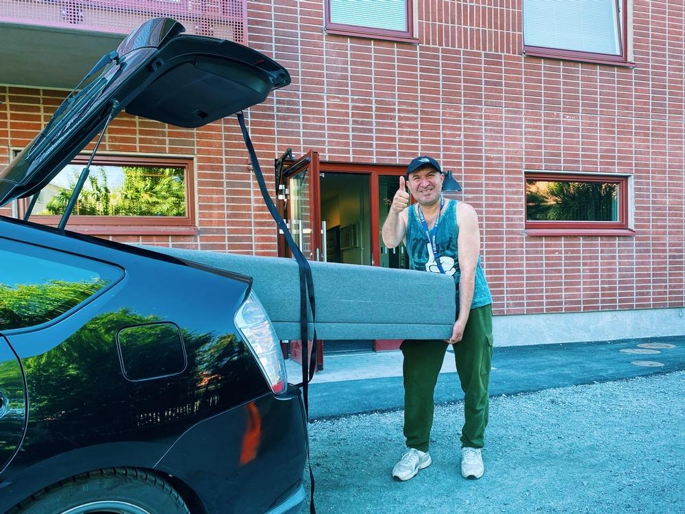 En man lastar ur en säng från bagageutrymmet från en bil som står utanför porten till ett bostadshus.