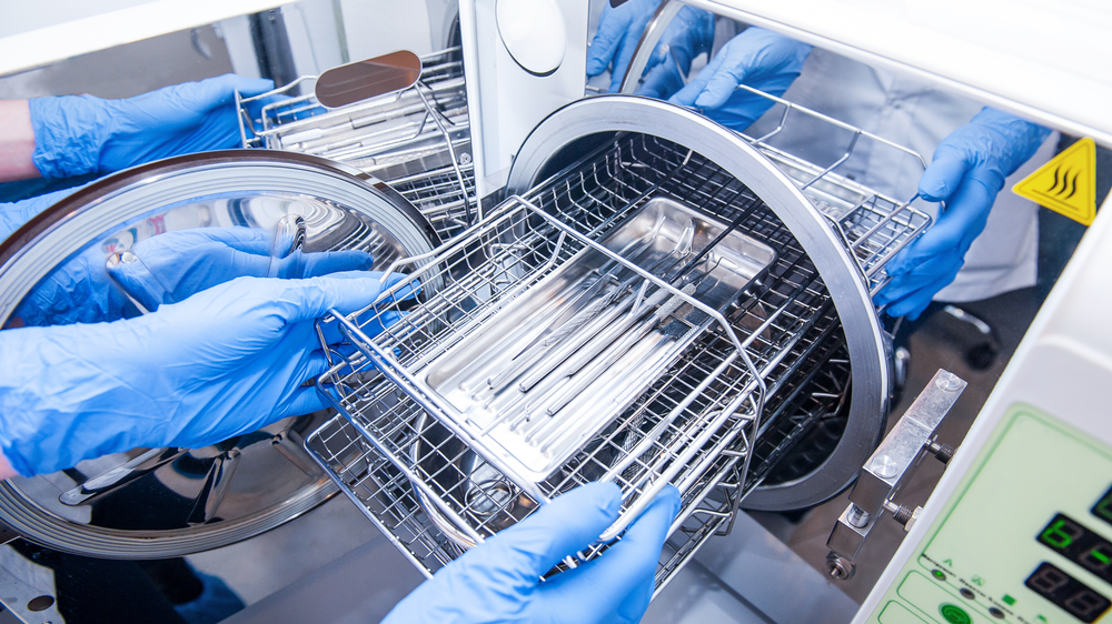 A technician inserts dental instruments into an autoclave for steam sterilization.