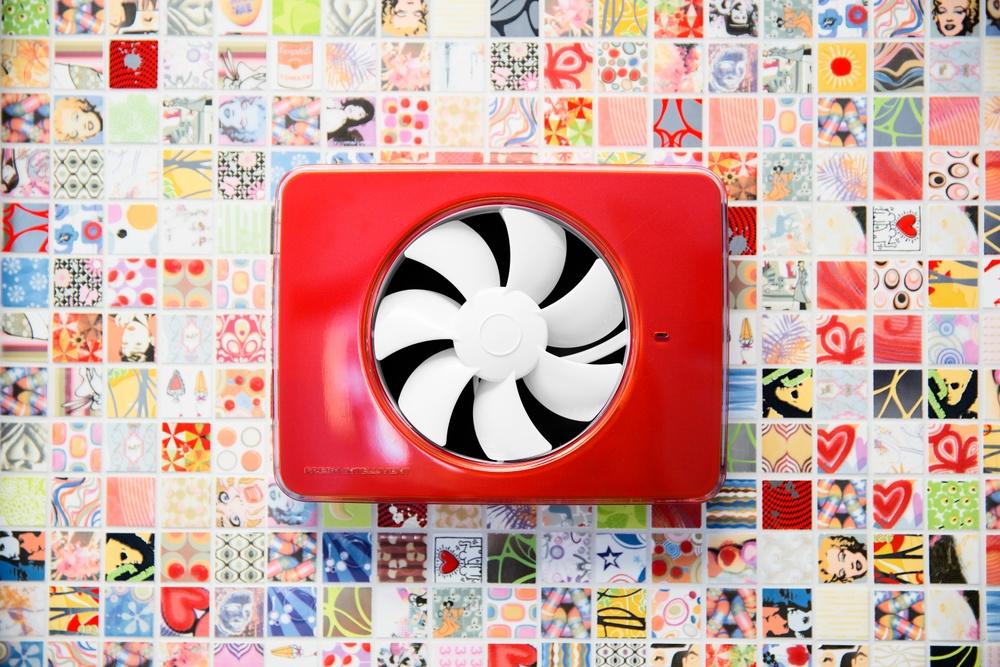 En röd Fresh Intellivent sitter på en färgglad och mönstrad mosaikvägg.