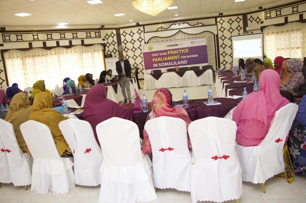 Konferenslokal med ett tjugotal kvinnor i hijabs som sitter u-format.