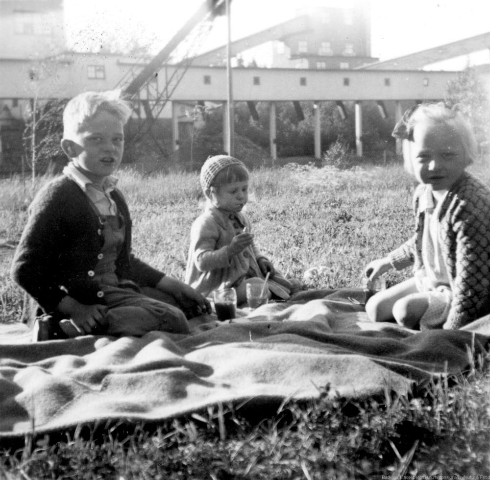 Svartvit bild på ttre barn som sitter på en filt i gräset vid Sripa gruva.