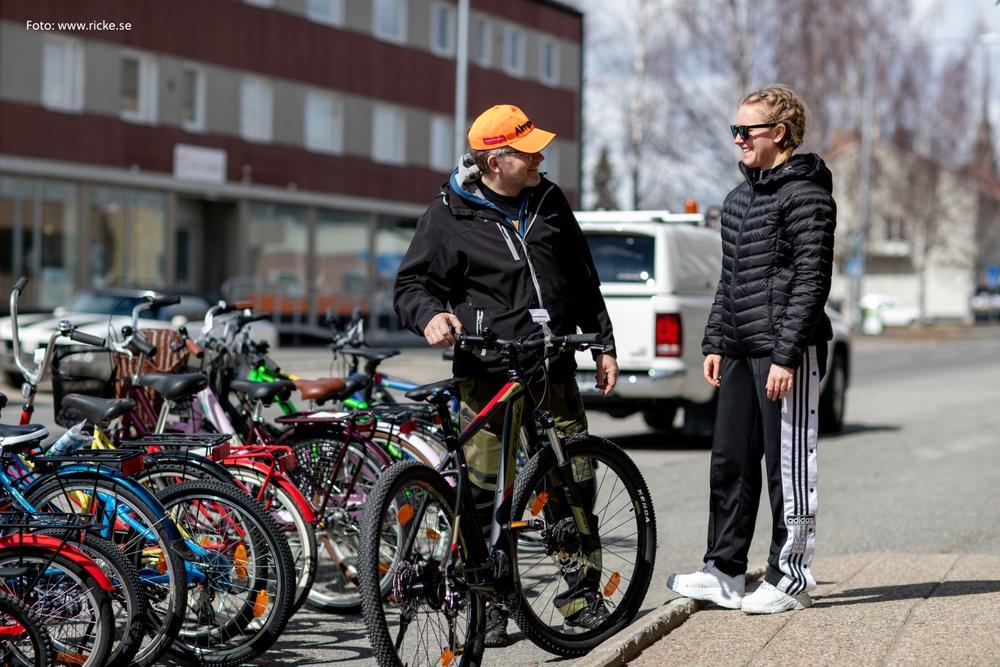 Två personer, en man och en kvinna, som pratar med varandra. Mannen har orange keps, svarta kläder och lutar sig mot en cykel. Kvinnan har solglasögon och svarta kläder.