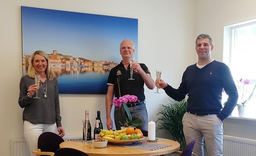 Bilden visar medarbetarna i Kungälv när de firar flytt till nya lokaler med champangeskål.