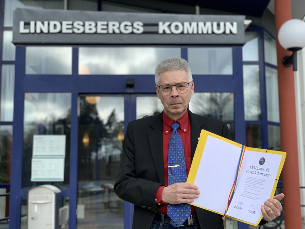 Kommunfullmäktiges ordförande Arnold Bengtsson står framför kommunhuset i Lindesberg med Deklarationen för stark demokrati i handen.