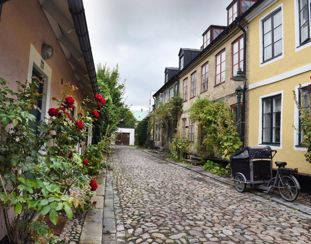 Om du står precis här på Stora Sigridsgatan i Lund, med vy mot Domkyrkan, då står du på den plats där två män begravdes för 1000 respektive 900 år sedan, och sedan hittades igen hösten 2017. Helene Wilhelmson, osteolog och arkeolog, berättar i sin artikel i årsboken om sina analyser av kvarlevorna. Mannen i den äldre graven hade skorna på sig för att vara redo för återuppståndelsen. Efter 100 år i ensamhet fick han en granne som begravdes ovanpå. Nu finns bådas kvarlevor i Kulturens magasin, och fjärrvärmerör har tagit deras plats.  Foto: Nelly Hercberg, Kulturen