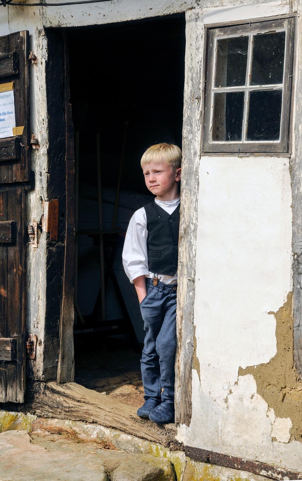 Pojke i dörröppning Gamlegård på Kulturens Östarp. Foto: Viveca Ohlsson/Kulturen