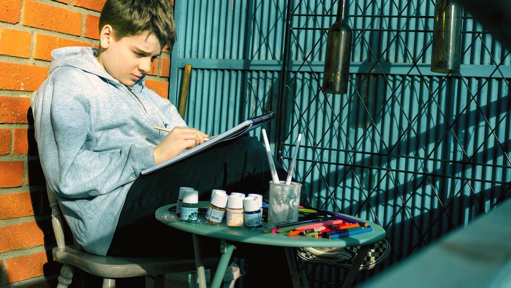 Pojke sitter på en blakong och målar