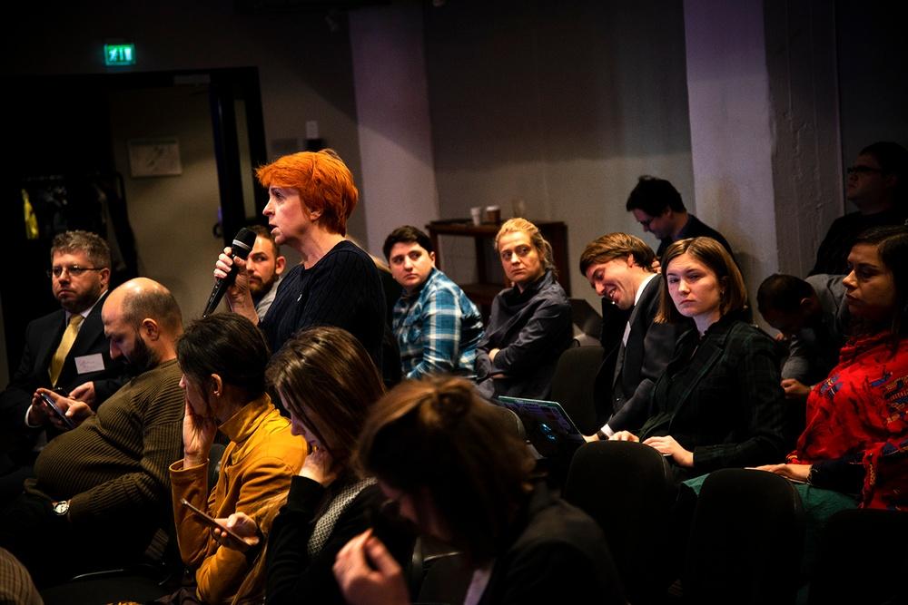 Lilia står upp mitt i publiken för att säga sin fråga. Åskådarna tittar intresserat.