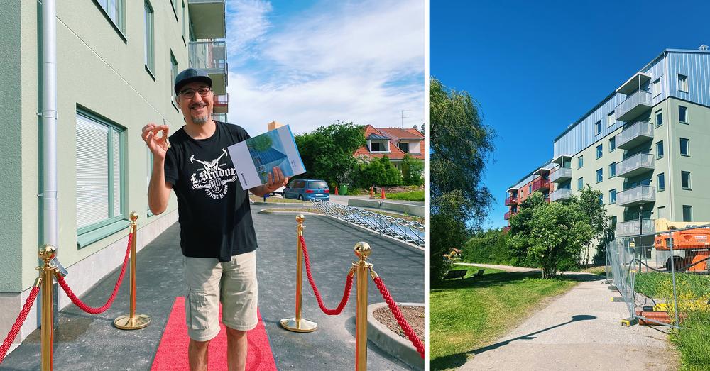 En glad man står på en röd matta bredvid ett bostadshus. I handen håller han upp ett par nycklar och en broschyr.