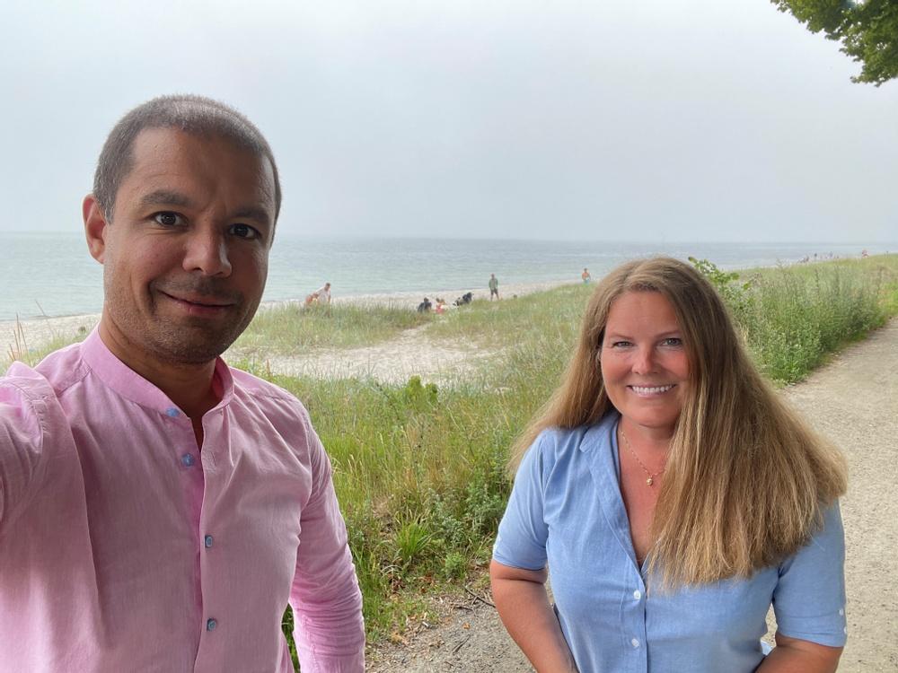 Sahand och Anne står på en cykelväg med havet och stranden i bakgrunden