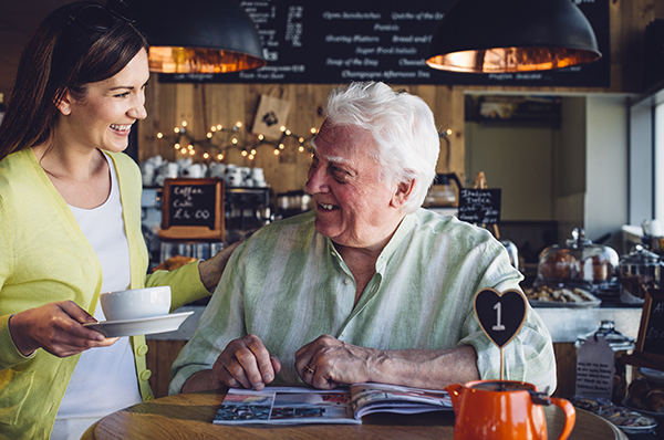 A very happy older man is sitting at a table in a cafe with a magazine open in front of him. He is smiling at the woman bringing him his hot drink.