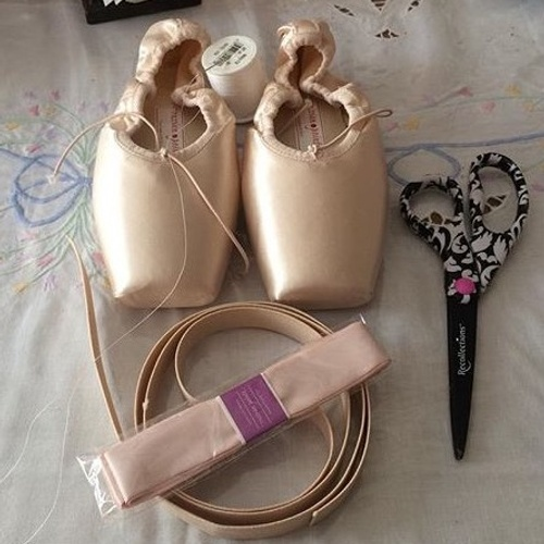 Sewing ribbons onto pointe shoes.