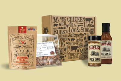 A cooking subscription box with labels for chicken, lamb and rubs, surrounded by Salt Lick barbecue sauce and dry rub.