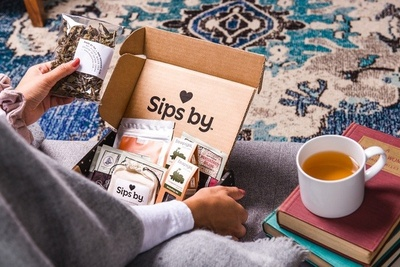 A woman opens a Sips by subscription box with various types of loose leaf tea and bagged tea.