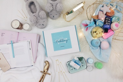 A closed Bath Bevy subscription box surrounded by bath bombs, soaps, bubbles, bunny slippers, candles and a mirror.