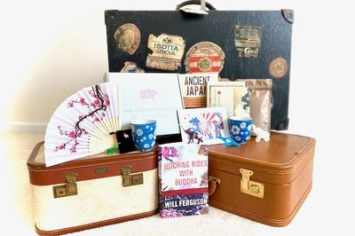 3 vintage suitcases with items from a Wordy Traveler subscription box on them, including books, mugs and a fan.