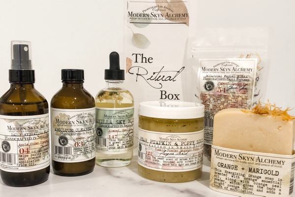 Items from a Modern Skyn Apothecary subscription box including a cleanser, hydrating spray, body scrub and soap.