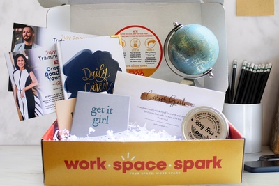 A Work Space Spark subscription box with a few small notebooks, a journal, and a ring toss game.