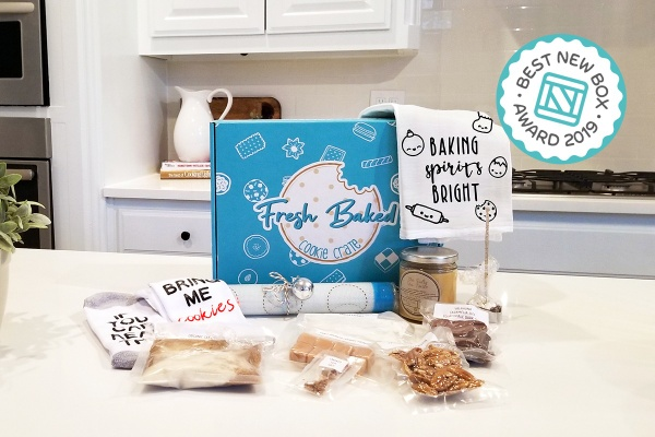 A cooking subscription box labeled Fresh Baked Cookie Crate surrounded by clear packets of ingredients and cute hand towels.