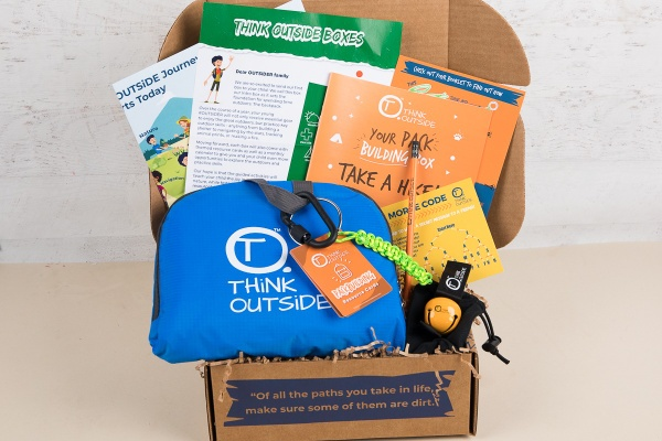 A Think Outside subscription box filled with a blue, zippered pouch, instructions and cards for learning outside.