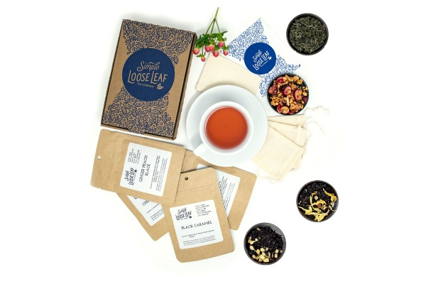 A Simple Loose Leaf subscription box with a cup of tea, 4 bowls of loose leaf tea, and several packets of tea.