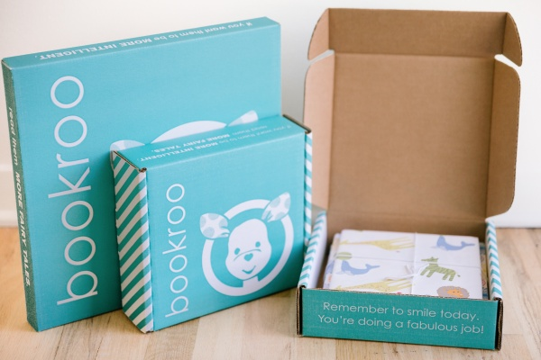2 closed Bookroo subscription boxes sitting next to an open box that contains a baby book.