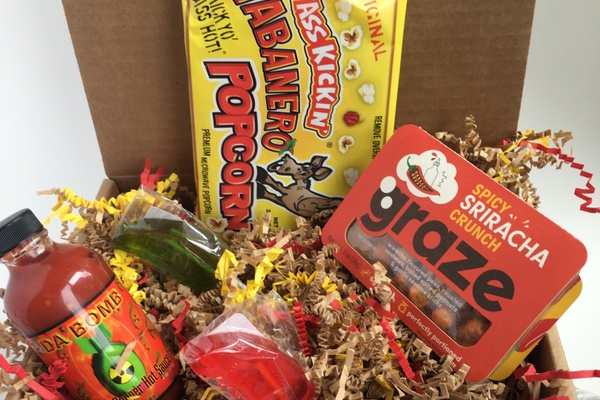 The Scorchin' Hot subscription box filled with spicy sriracha graze, habanero popcorn, Da Bomb hot sauce and other snacks.