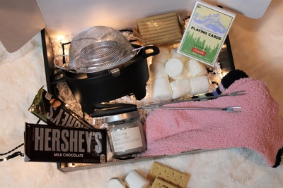 Items from a Krush Date Night subscription box, including Hershey's bars, marshmallows, graham crackers and fondue pot.