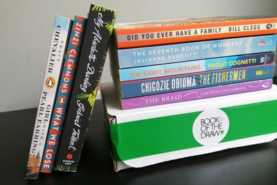 A closed Book of the Draw subscription box with several books on top of it and leaning against it.