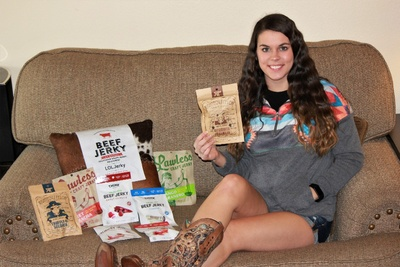A woman sitting on a couch holding a pack of beef jerky, next to a bunch of products from a LOLJerky subscription box.