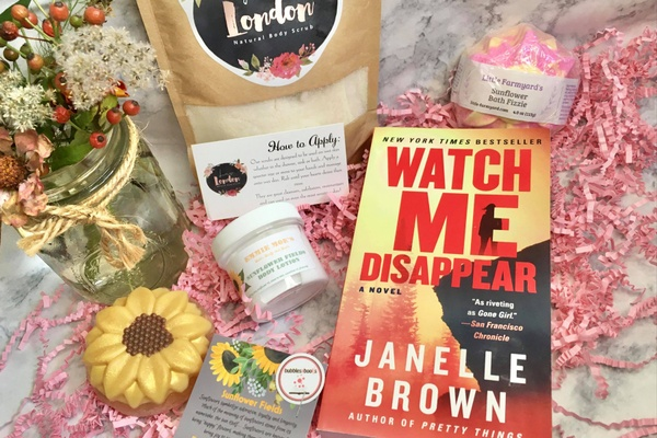 Items from a Bubbles and Books subscription box, including a book, a sunflower bath fizzle, body scrub and body lotion.