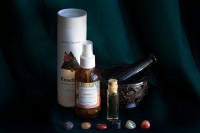 Items from a Herbalism and Ceremony subscription box including small colored stones, oils and fragrances.