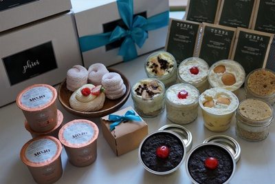 Phivi subscription boxes stacked with a variety of desserts in front, including cookies, meringue and others.
